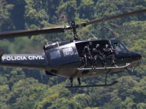 Schwaerzer Hubschrauber über Favela in Brasilien